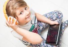 Unga barnet ?r lyssnande musik med headphonen p? minnestavlan royaltyfri foto