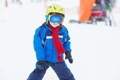 Unga barnet som skidar på snölutning skidar in, semesterorten i Österrike Fotografering för Bildbyråer