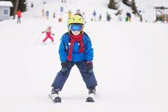 Unga barnet som skidar på snölutning skidar in, semesterorten i Österrike Royaltyfria Bilder