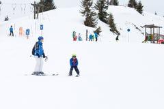 Unga barnet som skidar på snölutning skidar in, semesterorten i Österrike Arkivfoto
