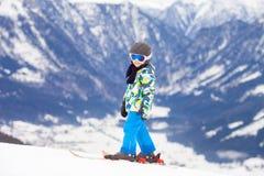Unga barnet som skidar på snölutning skidar in, semesterorten i Österrike Royaltyfri Bild
