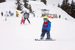 Unga barnet som skidar på snölutning skidar in, semesterorten i Österrike Royaltyfri Fotografi