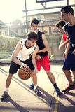 Unga basketspelare som spelar med energi Arkivbild