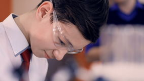Unga blandande flytande för skolapojke i provrör i vetenskapsgrupp lager videofilmer