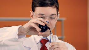 Unga blandande flytande för skolapojke i provrör i vetenskapsgrupp stock video