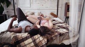 Unga blandras- par i pyjamas som ligger på sängen och ser foto Man- och kvinnabrukssmartphone med pekskärmen Royaltyfri Foto