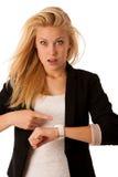 Unga blonda kvinnablickar på hennes klocka, när hon skulle vara sen iso royaltyfri fotografi