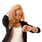 Unga blonda kvinnablickar på hennes klocka, när hon skulle vara sen iso Royaltyfria Bilder