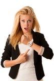Unga blonda kvinnablickar på hennes klocka, när hon skulle vara sen iso Arkivbilder