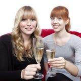 Unga blonda och röda haired flickor med champagne Arkivbilder