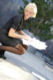 Unga blonda papperen för en affärskvinnaholding Fotografering för Bildbyråer