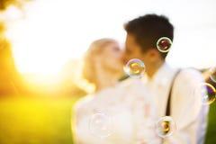 Unga brölloppar på en sommaräng royaltyfria bilder
