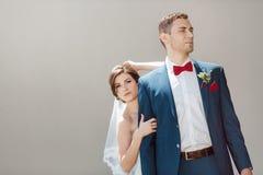 Unga brölloppar som är allvarliga mot en grå vägg arkivfoton