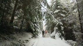 Unga brölloppar som går, ler och talar rymma händer i snöig skog under snöfall brudbrudgum som gifta sig utomhus vinter