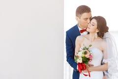 Unga brölloppar som kysser nära en grå vägg royaltyfri foto