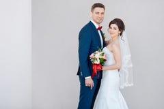 Unga brölloppar som ler mot en grå vägg royaltyfria bilder