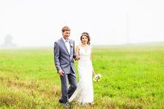 Unga brölloppar som utomhus går royaltyfria bilder