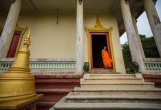 Unga buddistiska munkar går ut ur klosterdörröppningen Arkivbild