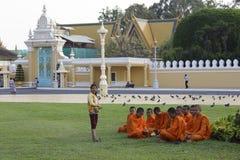 Unga buddistiska munkar i en trädgård, Phnom Penh, Cambodja Royaltyfri Bild