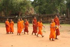Unga buddistiska munkar på vägen till bönen nära Angkor, Cambodja arkivbilder