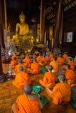 Unga buddistiska munkar som framme ber av Buddhabilden Arkivfoto