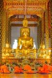 Unga buddistiska munkar som framme ber av Buddhabilden Fotografering för Bildbyråer