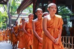 Unga buddistiska munkar som går i linje Arkivbild