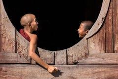 Unga buddistiska munkar som skrattar på ett fönster Arkivbilder