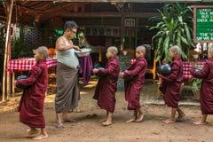 Unga buddistiska noviser går till mot efterkrav allmosa och offerings på gatorna av Bagan, Myanmar Royaltyfria Foton