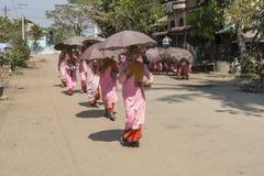 Unga buddistiska nunnor som samlar morgonallmosa Arkivbild