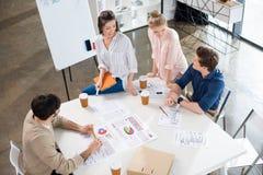 Unga businesspeople som diskuterar diagram på arbetsplatsen royaltyfri fotografi