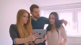 Unga caucasian par för fastighetsmäklarevisning den till salu demonstreringen för lägenhet och diskutera av använda för tillfälle stock video