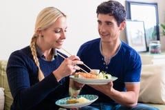 Unga Caucasian par som hemma äter asiatisk traditionell mat arkivfoto