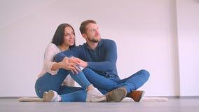 Unga caucasian par som sitter på golv av den nya tomma lägenheten som kramar och kysser vara lyckligt på vit väggbakgrund stock video