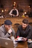 Unga chefer som kontrollerar dokument av hans bar med bartendern som göras suddig i bakgrunden arkivfoto