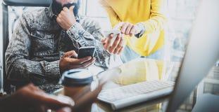 Unga coworkers som arbetar på kontoret Kollegor som använder elektroniska grejer och smartphones i modern arbetsplats horisontal Fotografering för Bildbyråer