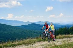 Unga cyklistturister, man och kvinna i yrkesmässig sportswear som rider cyklar ner den gräs- fältvägen royaltyfri fotografi