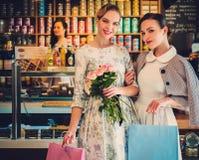 Unga damer som shoppar i ett bageri arkivbild