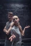 Unga dansare som framme står av den svarta väggen Arkivfoton