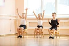 Unga dansare som spelar eller gör övning, medan sitta på stolar Arkivbilder