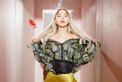 Unga den iklädda modeflickabloggeren ett stilfullt svart och gult omslag och gula kortslutningar poserar i en provhytt av royaltyfria foton