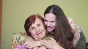 Unga dotterinställningar och krama försiktigt åldringmodern stock video