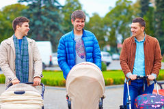 Unga fäder med behandla som ett barn sittvagnar på stad går Royaltyfri Foto