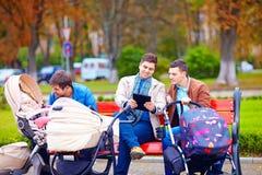 Unga fäder med behandla som ett barn sittvagnar på stad går Royaltyfria Bilder