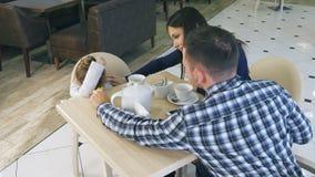 Unga föräldrar försöker att lugna deras lilla frustrerade dotter i kafé lager videofilmer