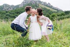 Unga föräldrar i bröllopsklänningar kysser deras unga dotter i kinder Fotografering för Bildbyråer