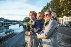 Unga föräldrar med deras litet barnson som utomhus står vid floden i stad royaltyfria bilder
