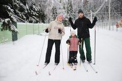 Unga föräldrar och deras dotter gör nordisk skidåkning Royaltyfri Bild