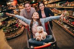 Unga föräldrar och dotter i livsmedelsbutik Den skämtsamma flickan har leksakbjörnen på knä Hon låtsar flyg Förälderanseende arkivfoton