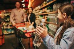 Unga föräldrar och dotter i livsmedelsbutik Flaska för liten flickahållvatten i händer och blick på föräldrar De står arkivbilder